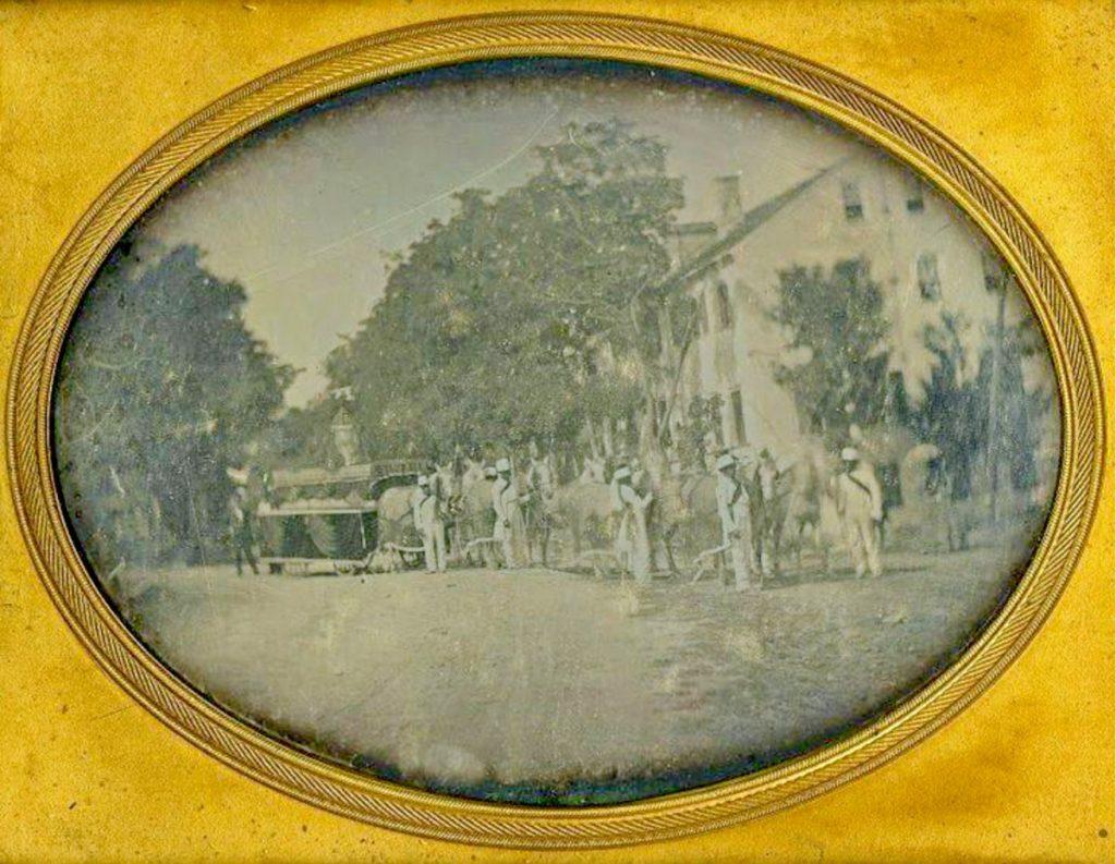 Men in uniform accompany a horse-drawn hearse.