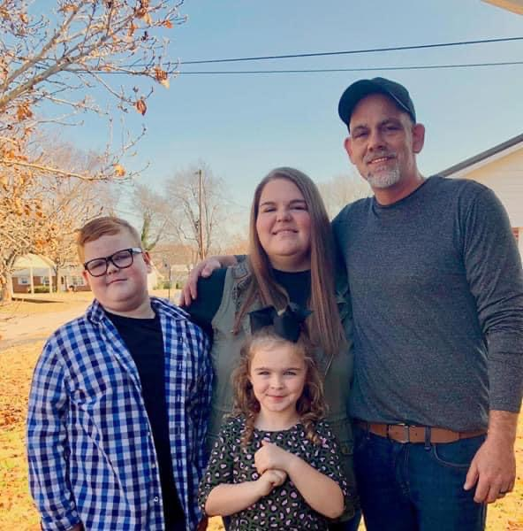 A true family man, John Elmore, right, was a devoted husband and father. Pictured with John is his wife Laura, son Evan, and daughter Charli. Photo submitted.